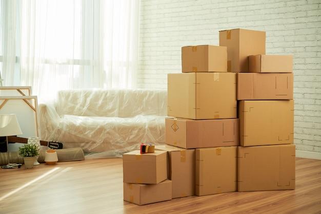 Foto do interior da sala com caixas de embalagem em pé no meio e sofá coberto com filme