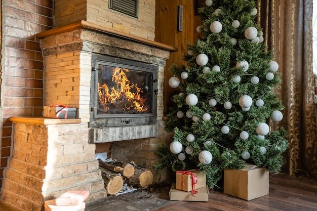 Foto do interior da sala com uma parede de madeira, árvore de natal, lareira. atmosfera de natal. conforto de casa