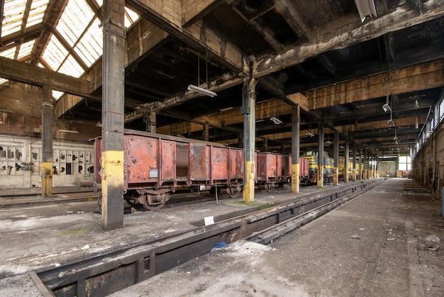 Foto do interior de um antigo armazém com trens antigos armazenados dentro