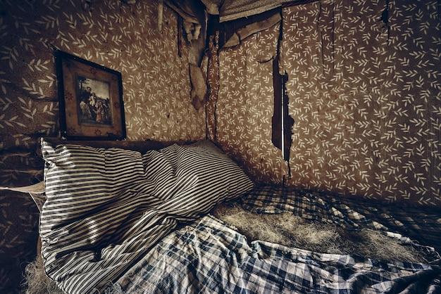 Foto do interior de um antigo quarto abandonado com paredes quebradas