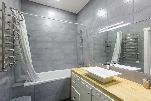 Foto do interior de um banheiro moderno com azulejos cinza em um pequeno apartamento