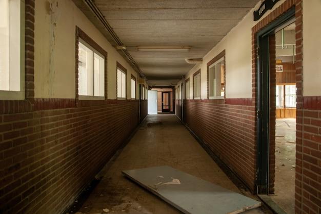 Foto do interior de um corredor vazio de uma escola abandonada com portas quebradas