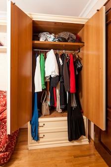 Foto do interior do guarda-roupa com roupas em cabides