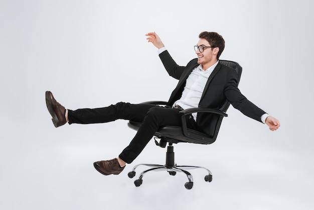 Foto do jovem empresário caucasiano sentado na cadeira. isolado sobre a parede branca. olhe para o lado.