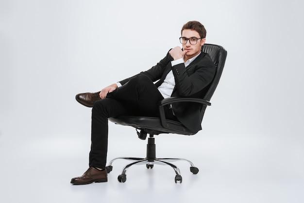 Foto do jovem empresário sentado na cadeira. isolado sobre a parede branca.