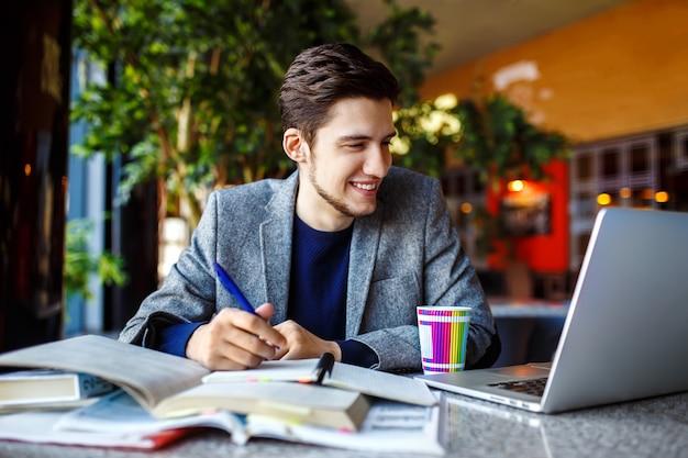 Foto do jovem estudante do sexo masculino sentado à mesa e escrevendo no caderno. jovem estudante do sexo masculino estudando no café.