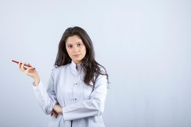 Foto do jovem médico segurando o celular em cinza.