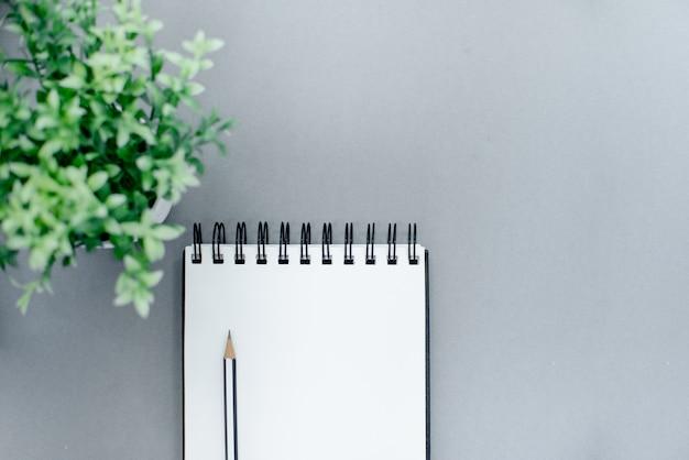 Foto do lápis e do bloco de notas em um fundo abstrato cinzento