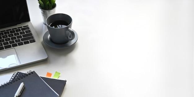 Foto do laptop do computador, xícara de café, caderno, diário, caneta, planta em vaso, colocando sobre a mesa de trabalho branca. conceito de local de trabalho em ordem.