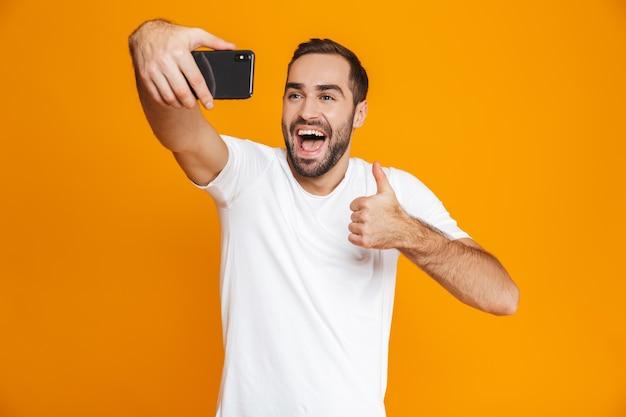 Foto do lindo cara dos 30 anos em roupa casual rindo e tirando selfie no celular