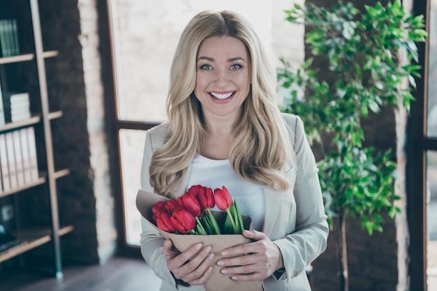 Foto do local de trabalho da mulher de negócios segurando um sorriso cheio de tulipas frescas
