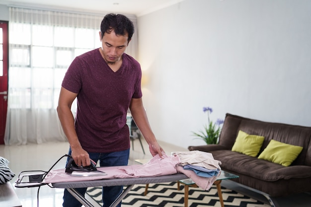 Foto do marido responsável ou solteiro ocupado com o trabalho doméstico, passa a camisa pela manhã na mesa de passar roupa antes do trabalho,