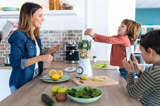 Foto do menino ajudando a mãe a preparar um suco desintoxicante no liquidificador enquanto o irmão tira fotos com o celular na cozinha de casa.