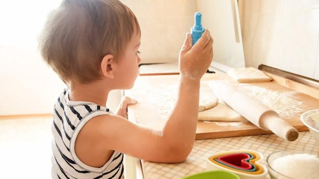 Foto do menino da criança de 3 anos rolando massa na placa de madeira e assando biscoitos no café da manhã. criança cozinhando na cozinha