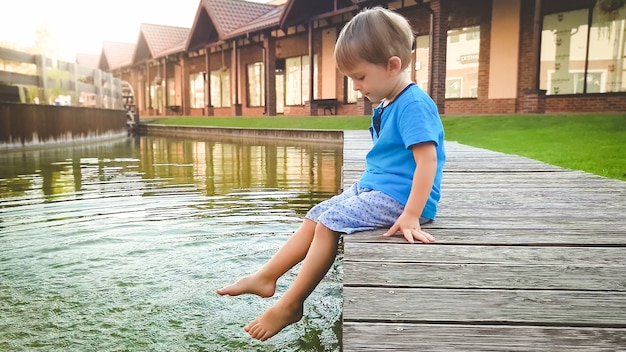 Foto do menino fofo de 3 anos de idade, sentado no riverebank no canal de água na cidade velha e espirrando água com os pés.