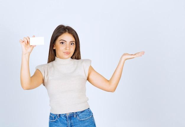 Foto do modelo de mulher jovem e bonita segurando um cartão e mostrando uma mão.