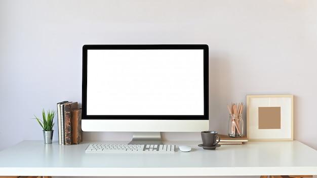 Foto do monitor do computador com tela em branco branca, pilha de livros, planta em vaso, teclado sem fio, mouse, copo de café, porta-lápis e porta-retrato montando na mesa de trabalho branca.