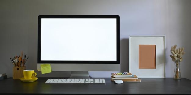 Foto do monitor do computador da tela em branco do espaço de trabalho que põe sobre a mesa de trabalho e cercada pela moldura para retrato, porta-lápis, pilha de livros, mouse sem fio, teclado, xícara de café e grama selvagem no vaso.