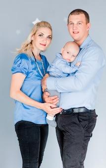 Foto do pai abraça sua esposa e filho. família feliz olhando para a câmera