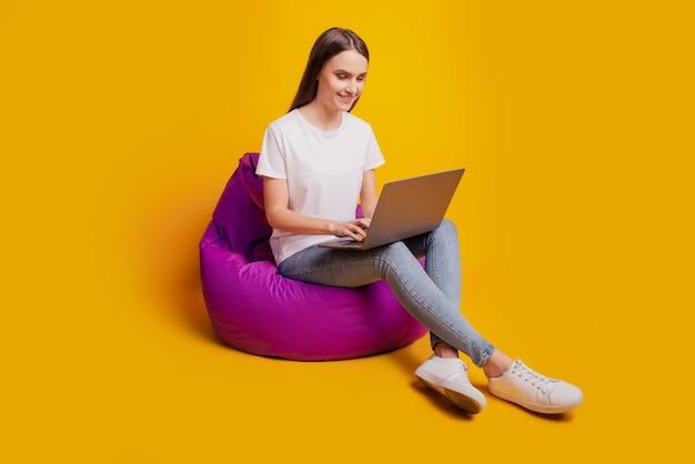 Foto do perfil da senhora sentada beanbag trabalho netbook vestindo camiseta branca posando em fundo amarelo