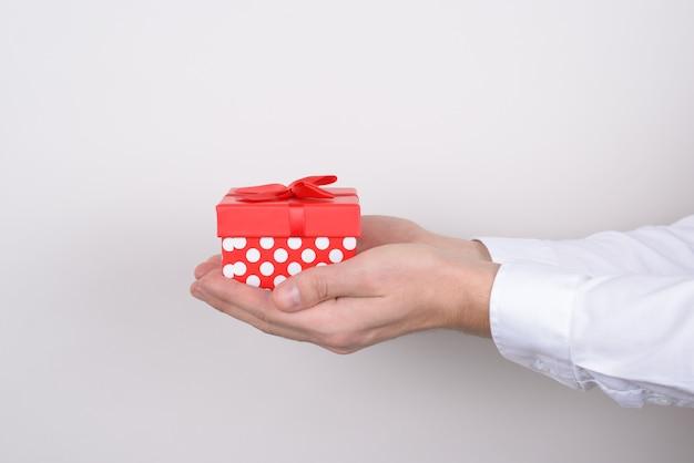 Foto do perfil de mãos segurando uma caixa de presente isolada em um fundo cinza