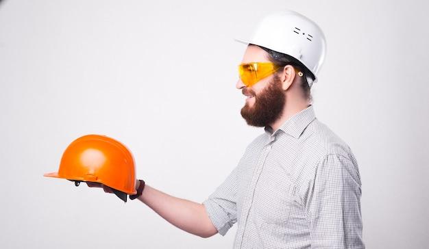 Foto do perfil de um belo arquiteto dando a alguém um capacete laranja para proteção