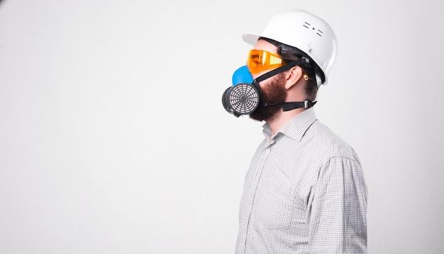 Foto do perfil de um homem de camisa, usando um capacete branco e respirando pelo respirador