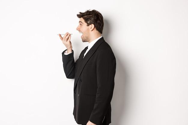 Foto do perfil de um homem de negócios bonito de terno preto falando no viva-voz