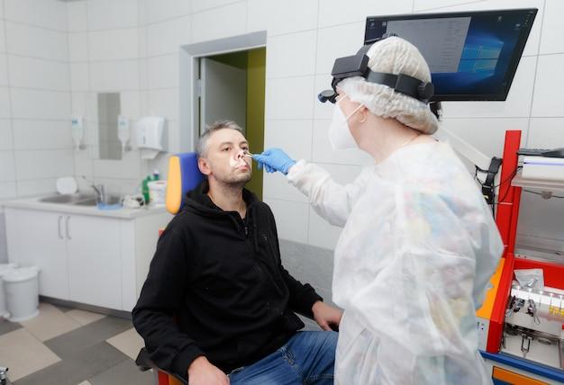 Foto do perfil de um otorrinolaringologista examinando o nariz de um paciente. escritório moderno.