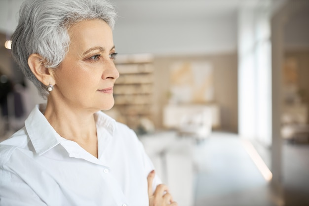 Foto do perfil de uma elegante empresária madura, vestindo uma camisa formal branca, em um escritório moderno