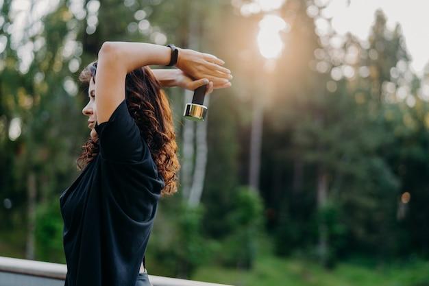Foto do perfil de uma jovem ativa e motivada, vestida com uma camiseta preta