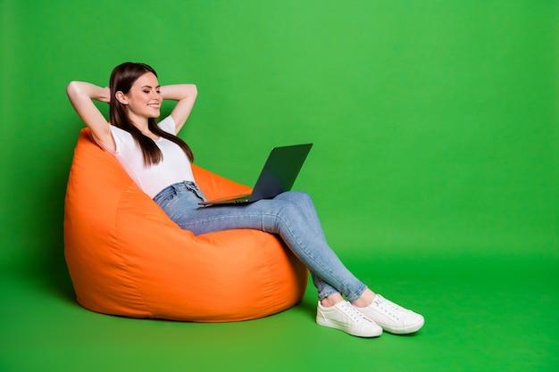 Foto do perfil de uma jovem muito alegre segurando as mãos do laptop atrás da cabeça. vestido com uma camiseta branca e tênis jeans isolado no fundo verde