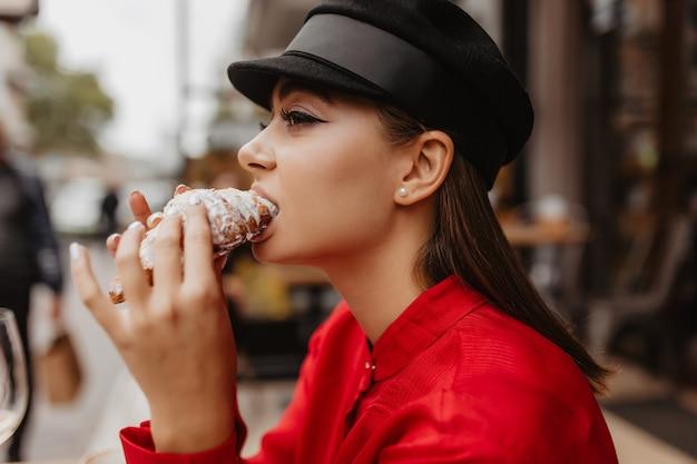 Foto do perfil de uma linda garota com cabelo castanho na boina. mulher saboreando a famosa sobremesa americana em um café de rua