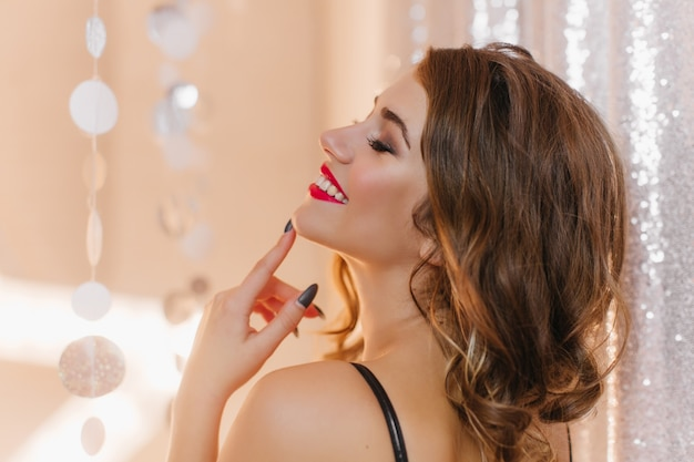 Foto do perfil de uma mulher atraente com maquiagem brilhante e manicure preta posando