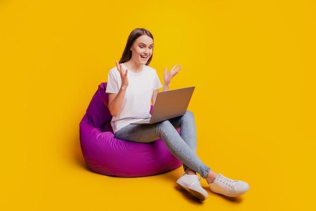 Foto do perfil de uma senhora animada, sentada no pufe, trabalhando no computador remoto, vestindo uma camiseta branca posando em um fundo amarelo
