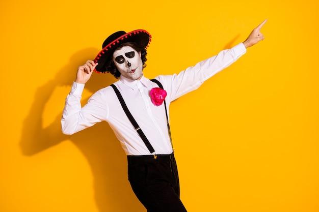 Foto do perfil do assustador cara carismático espanhol tradição dança segurar boné dedo direto espaço vazio vestir camisa branca rosa traje de morte suspensórios de sombrero isolado fundo de cor amarela