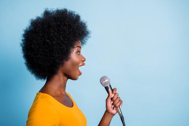 Foto do perfil lateral de uma garota bonita de pele negra cantando no microfone olhando para copyspace isolado em um fundo de cor azul brilhante