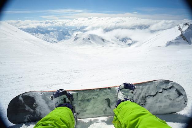 Foto do ponto de vista de um snowboarder masculino deitado na neve, relaxando depois de pedalar