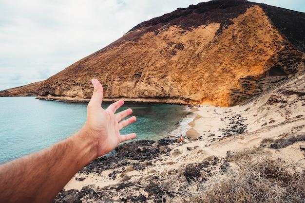 Foto do ponto de vista de uma mão masculina estendendo-se em direção à costa rochosa em playa amarilla, espanha