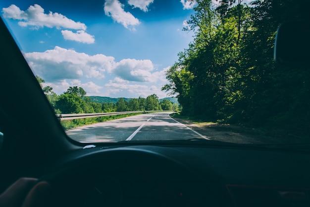 Foto do ponto de vista de uma pessoa dirigindo um veículo na estrada rural