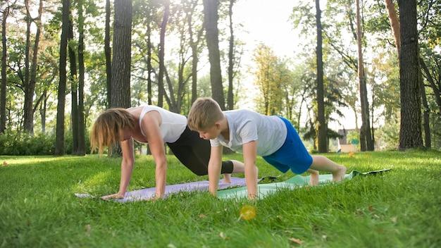 Foto do professor de ioga feminino de meia idade ou guru ensinando adolescente fazendo ioga. mulher com menino meditando e se espreguiçando na grama do parque