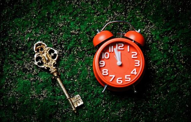 Foto do relógio e chave na grama verde
