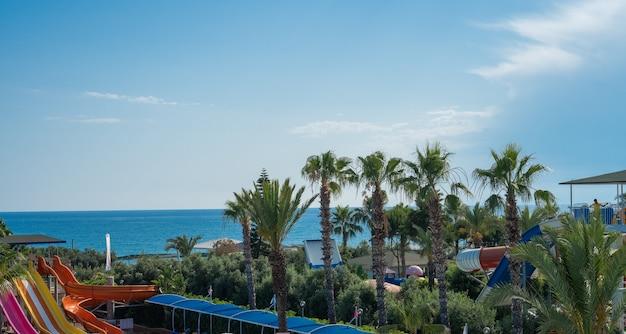 Foto do resort, com o mar e palmeiras, um lugar para relaxar no verão.