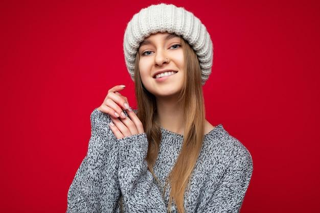 Foto do retrato da bela jovem loira escura sorridente sexy em pé isolado sobre a parede de fundo vermelho, vestindo uma camisola cinza e chapéu bege de inverno, olhando para a câmera.
