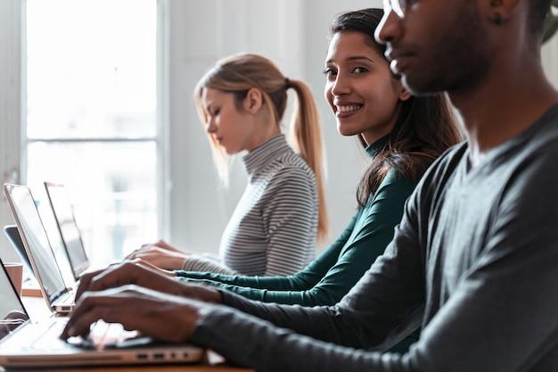 Foto do retrato da vista lateral de uma mulher de negócios que trabalha com o laptop entre outros colegas no local de coworking.