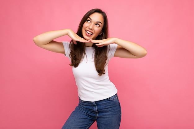 Foto do retrato de jovem feliz positivo sorridente linda mulher morena com emoções sinceras, vestindo camiseta branca casual para maquete isolada no fundo rosa com espaço de cópia.