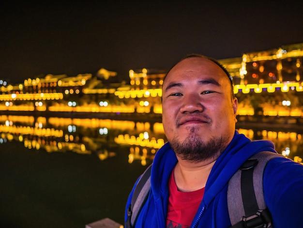 Foto do retrato de um mochileiro gordo asiático com uma bela vista do cenário na noite da cidade velha fenghuang