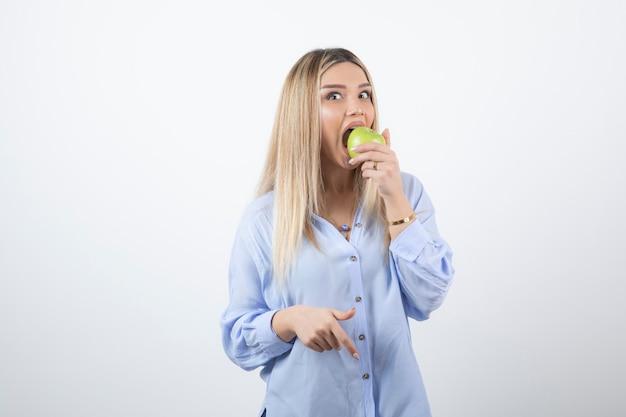 Foto do retrato de um modelo de mulher muito atraente em pé e comendo uma maçã verde fresca.