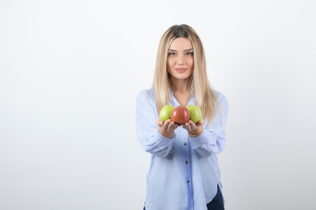Foto do retrato de um modelo de mulher muito atraente em pé e segurando maçãs frescas.