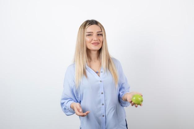 Foto do retrato de um modelo de mulher muito atraente em pé e segurando uma maçã verde fresca.